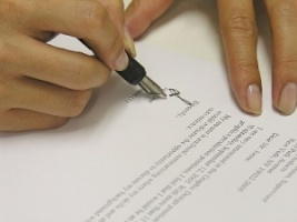 A photo of a woman signing a contract